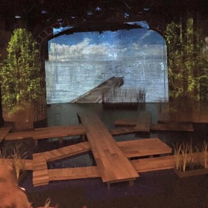 Michael Burden's gorgeous set design includes salvaged wood boardwalks and a swing to play on. Ian Knodel's lights and projections illuminate it beautifully.